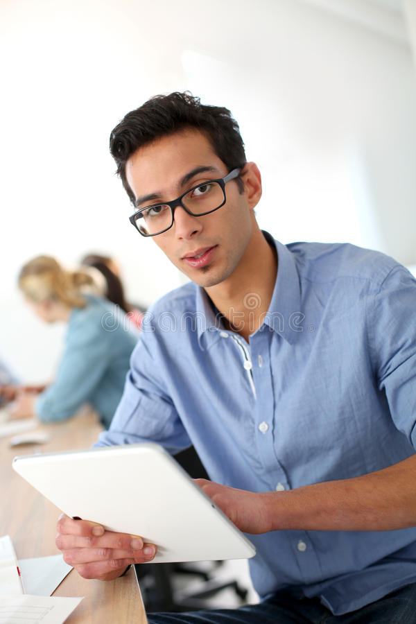 Portrait of man student in class. Student in class using digital tablet stock photos