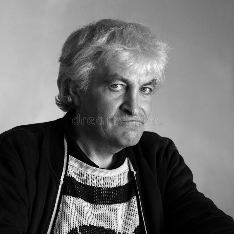 Portrait man style black white analog photography. Blonde 50 years old man in a black jacket and whitesweater looks directly into the lens. portrait in the style stock images