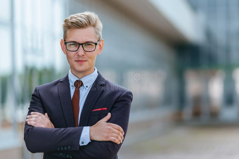 Portrait man in suit in front of office building. Handsome businessman outdoor. Male business person stands on street royalty free stock photos
