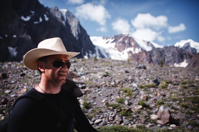 Portrait of a man in sunglasses and a hat with a walkie-talkie. Extreme trip to the mountains stock photography