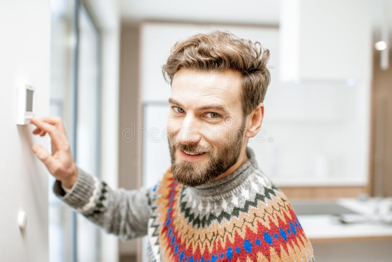 Man adjusting temperature with thermostat at home stock images