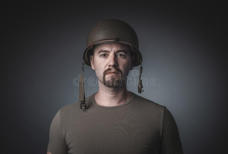 Portrait of a man in a t-shirt wearing a soldier`s military helmet royalty free stock photo