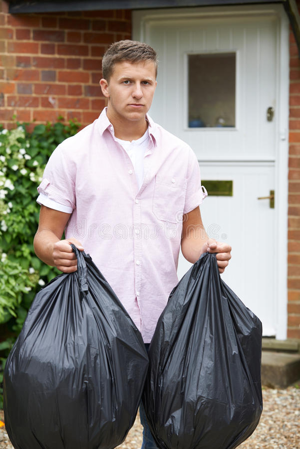 Portrait Of Man Taking Out Garbage In Bags. Man Taking Out Garbage In Bags royalty free stock photography