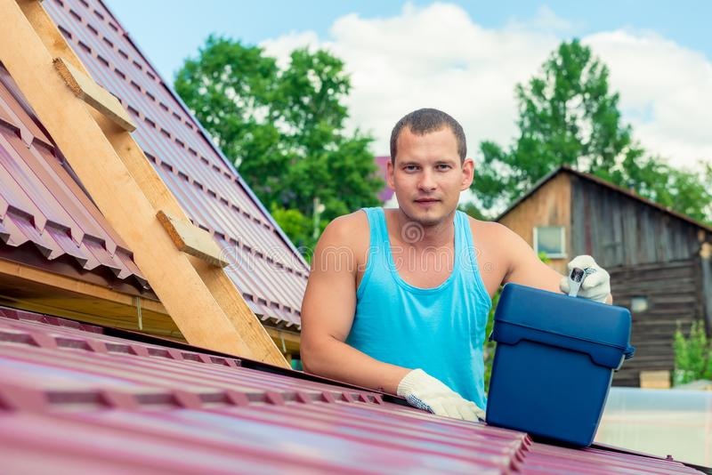Portrait of a man with a toolbox on the roof of the house stock photos