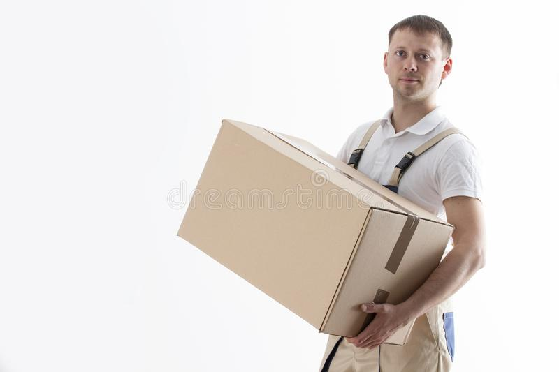 Portrait of man in uniform with cardboard box isolated on white background. Relocation service. Loader holds box royalty free stock image
