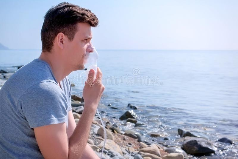 Portrait man uses nebulizer inhaler mask to treatment of fibrosis sits seaside. Portrait sick man uses nebulizer sits on seaside. Inhaling inhaler mask stock images