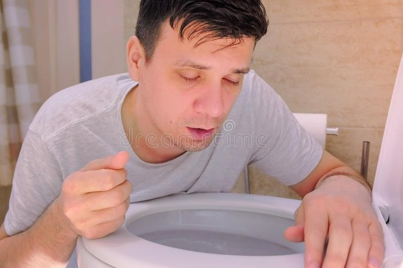 Portrait man vomiting in toilet after food poisoning with two fingers in mouth. royalty free stock image