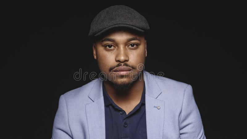 Portrait of a man wearing a cap. Close up of an african american businessman isolated on black background. Man wearing a suit and cap looking at camera royalty free stock photo