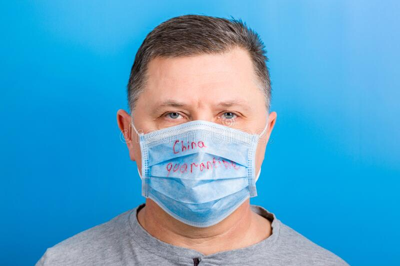 Portrait of man wearing medical mask with China quarantine word at blue background. Coronavirus concept. Respiratory protection.  stock photos