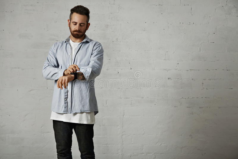 Portrait of a man in white t-shirt and denim. Young bearded hipster rolling up a sleeve of his casual light denim shirt showing tattoos on his arm in a studio stock photo