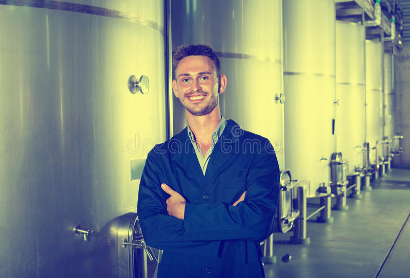 Portrait of man winery worker on wine factory in secondary fermentation section. Portrait of young smiling man winery worker standing on wine factory in stock photos