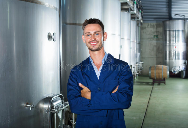 Portrait of man winery worker on wine factory in secondary fermentation section. Portrait of young man winery worker standing on wine factory in secondary royalty free stock photo