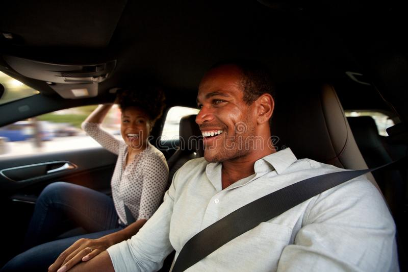 Portrait of man and woman sitting together in automobile smiling stock photography