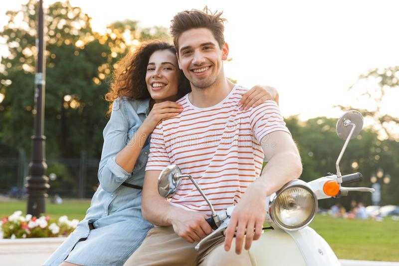 Portrait of man and woman smiling and hugging together while sitting on motorbike in city park royalty free stock photos