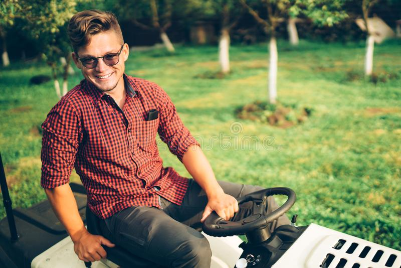Portrait of man working on ride-on lawn mower tractor. During landscaping in garden stock photo