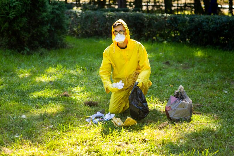 Portrait of a man in a yellow protective suit and mask. The man sat down and collected the garbage in a trash bag stock image