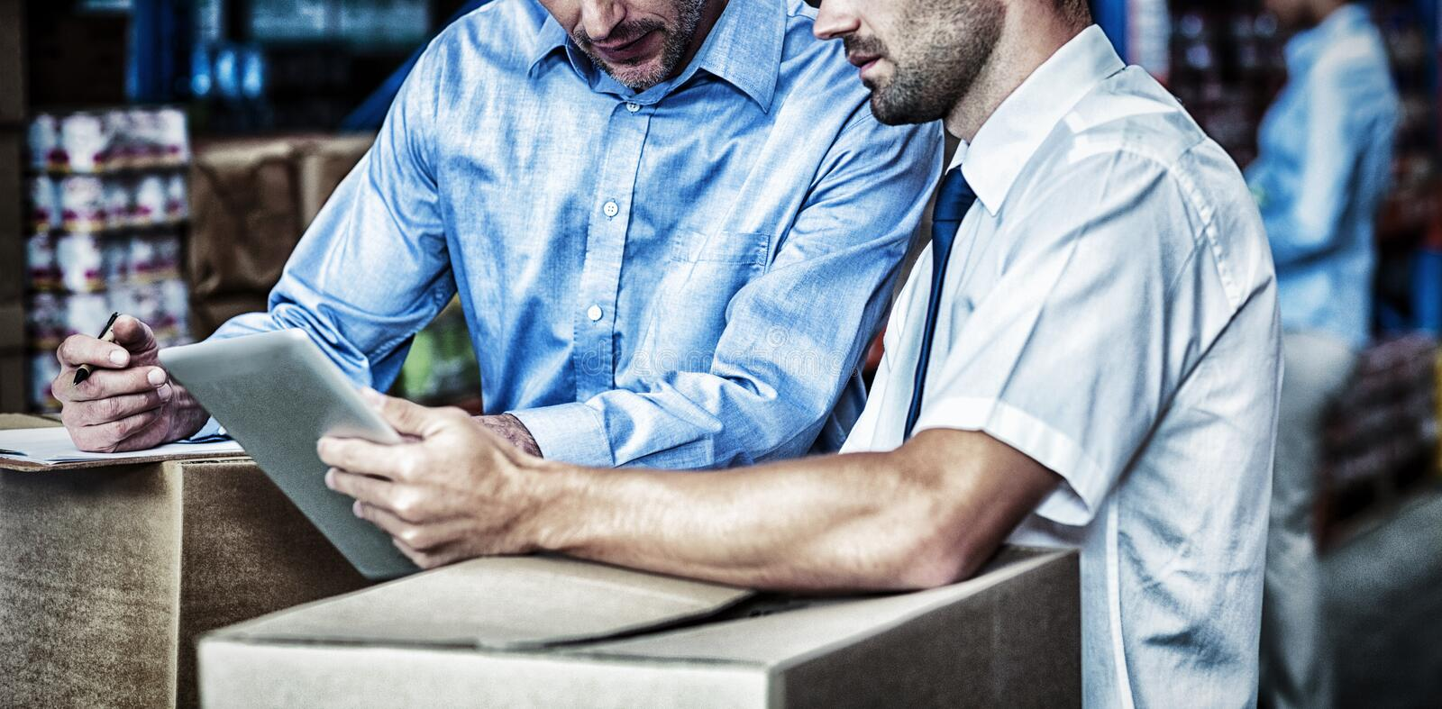 Portrait of managers are working with a tablet in the middle of cardboard boxes royalty free stock image