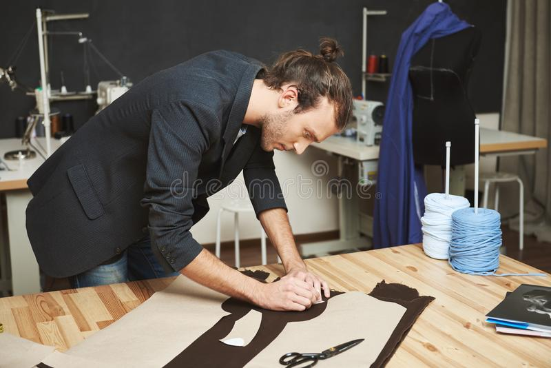Portrait of manly good-looking adult male clothes designer with stylish hairstyle in black suit cutting out parts of royalty free stock photo