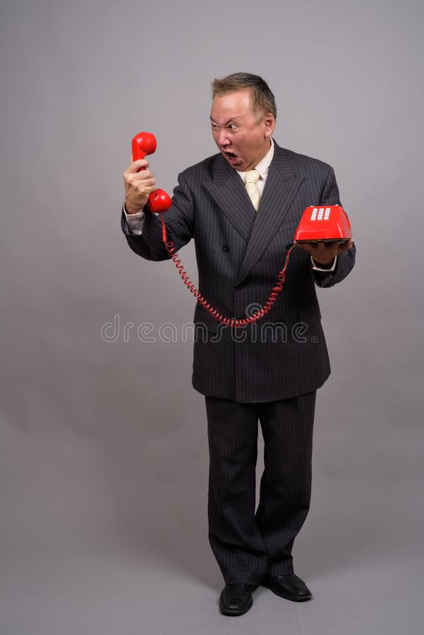 Portrait of mature Asian businessman against gray background stock images
