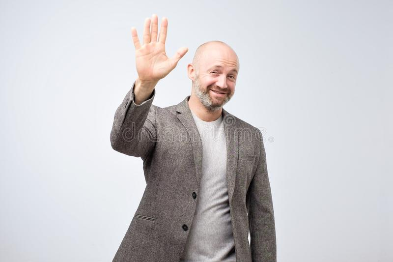 Portrait of a mature bald man in suit wave hand welcome. Human emotion expression and lifestyle concept. stock photos