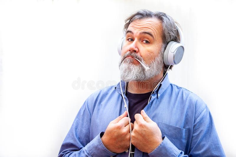Mature and bearded man enjoys and plays with his headphones on a white background stock photos