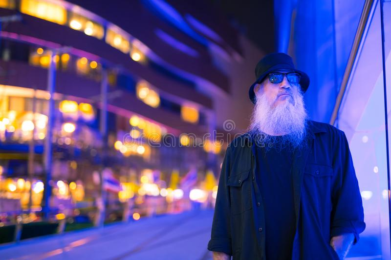 Mature bearded tourist man against blue light in the city streets at night. Portrait of mature bearded tourist man exploring the city streets of Bangkok royalty free stock photo