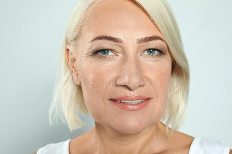 Portrait of mature  with beautiful face on grey background stock photo