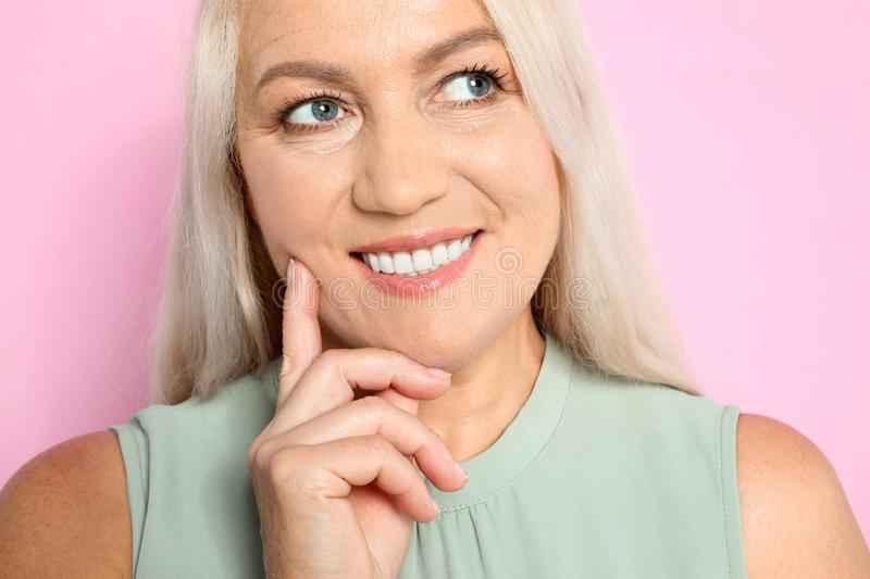 Portrait of mature  with beautiful face on pink background stock images