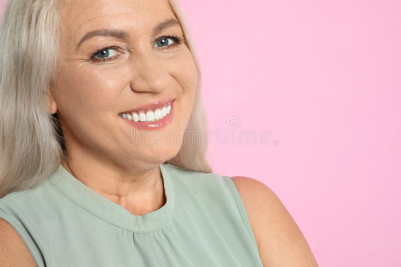 Portrait of mature  with beautiful face on pink background royalty free stock photography