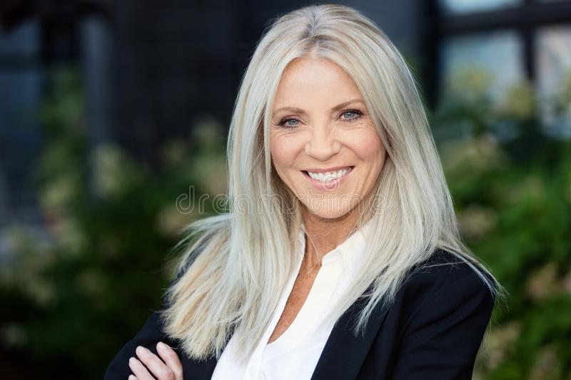 Portrait Of A Mature Blonde Businesswoman Smiling. Outside the office royalty free stock images