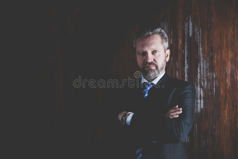 Portrait of a mature businessman on black background. Portrait of a mature businessman in a black suit on dark background stock photography