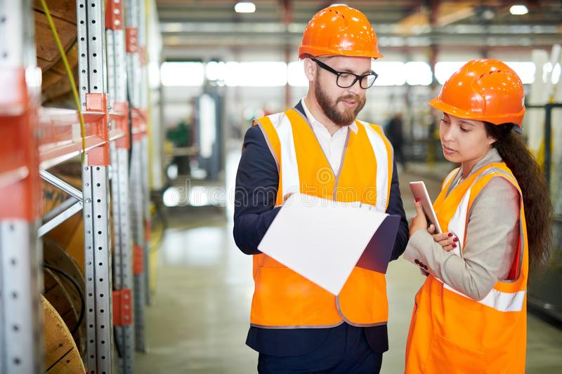 Factory Manager Talking to Employee. Portrait of mature businessman wearing hardhat talking to female factory worker standing by shelves in warehouse, copy space stock image