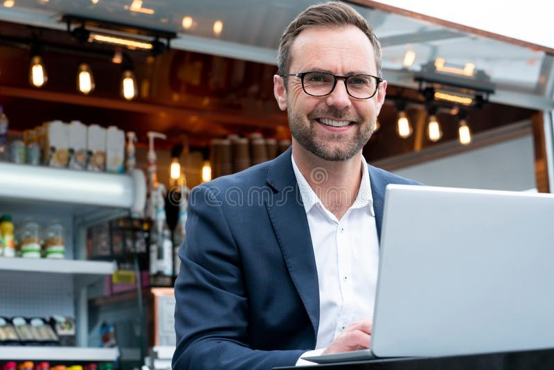 Portrait Of Mature Businessman Working On Laptop By Outdoor Coffee Shop royalty free stock photos