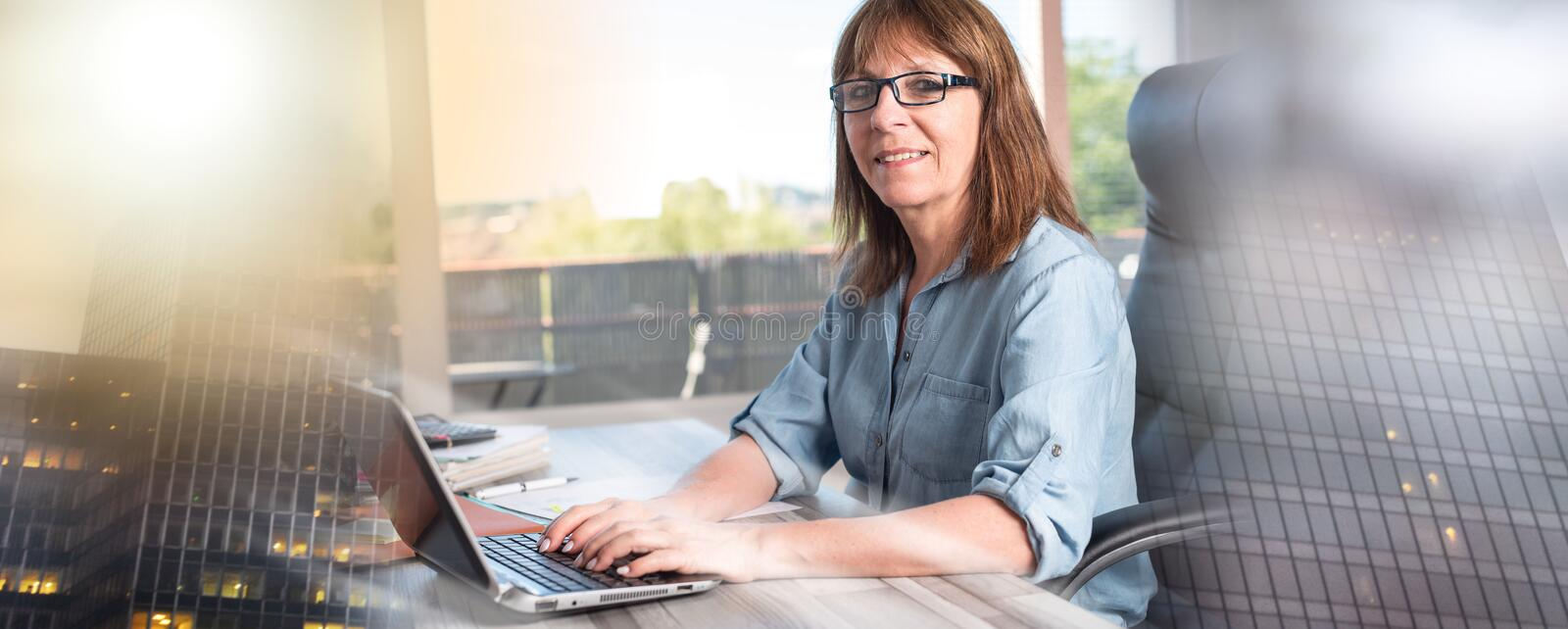 Portrait of mature businesswoman using a laptop; multiple exposure stock photo