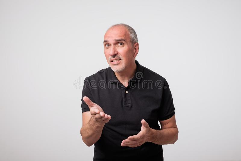 Portrait of mature caucasian a young man surprised and asking questions with hand raised. He is unsure and has doubts stock photos