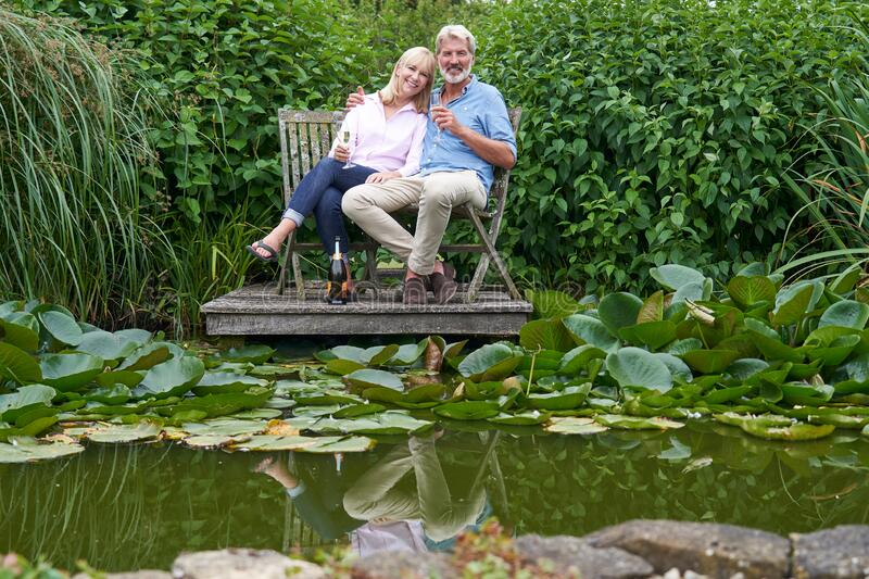 Portrait Of Mature Couple Celebrating With Champagne Sitting On Chairs On Wooden Jetty By Lake royalty free stock image
