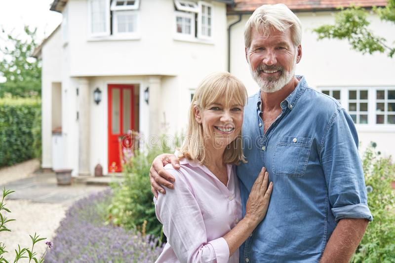 Portrait Of Mature Couple Standing In Garden In Front Of Dream Home In Countryside stock photography