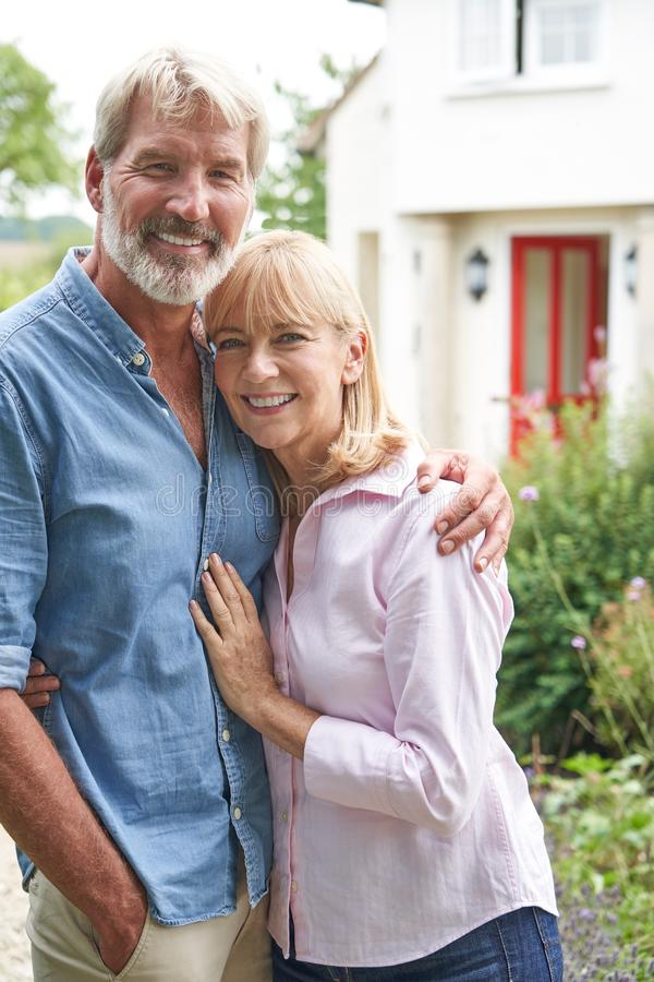 Portrait Of Mature Couple Standing In Garden In Front Of Dream Home In Countryside stock photos