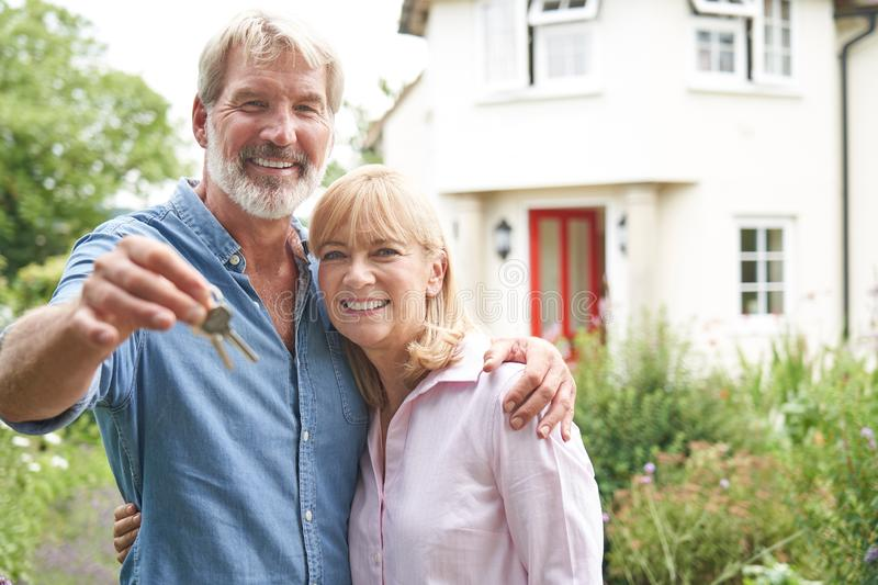 Portrait Of Mature Couple Standing In Garden In Front Of Dream Home In Countryside Holding Keys stock image