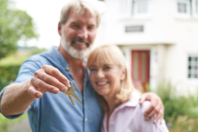 Portrait Of Mature Couple Standing In Garden In Front Of Dream Home In Countryside Holding Keys royalty free stock photo