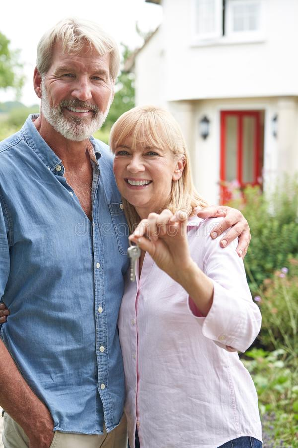 Portrait Of Mature Couple Standing In Garden In Front Of Dream Home In Countryside Holding Keys. Mature Couple Standing In Garden In Front Of Dream Home In stock photography