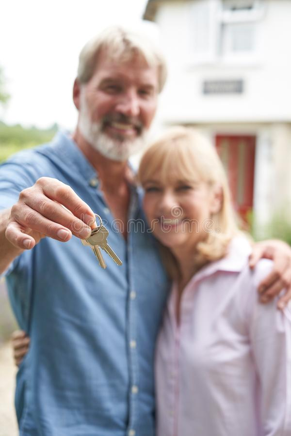 Portrait Of Mature Couple Standing In Garden In Front Of Dream Home In Countryside Holding Keys stock photos