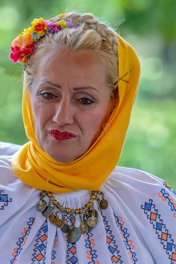 Portrait of mature dancer woman from Serbia in traditional costume. TIMISOARA, ROMANIA - JULY 7, 2019: Portrait of mature dancer woman from Serbia in traditional royalty free stock image