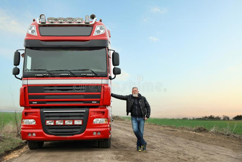 Portrait of mature driver closing door of modern truck. Outdoors stock photography