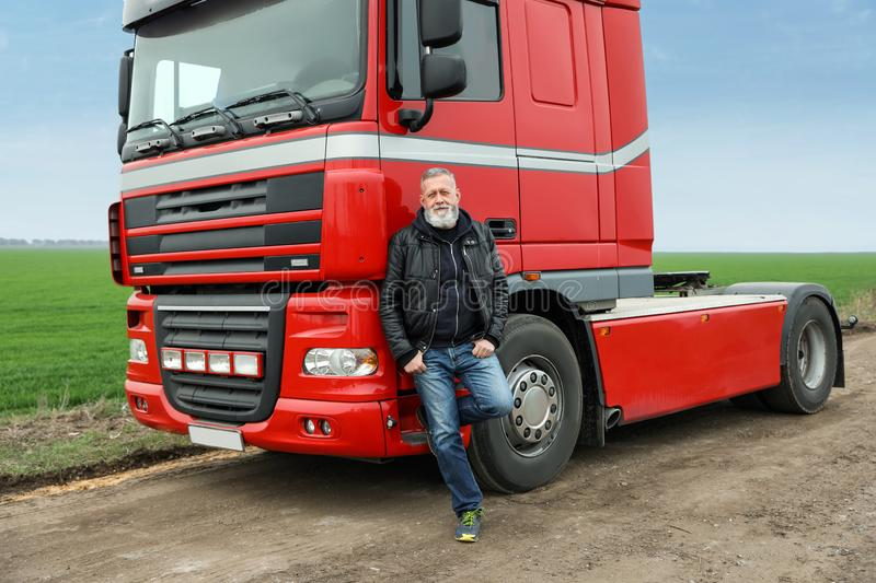 Portrait of mature driver at modern truck. Outdoors royalty free stock images