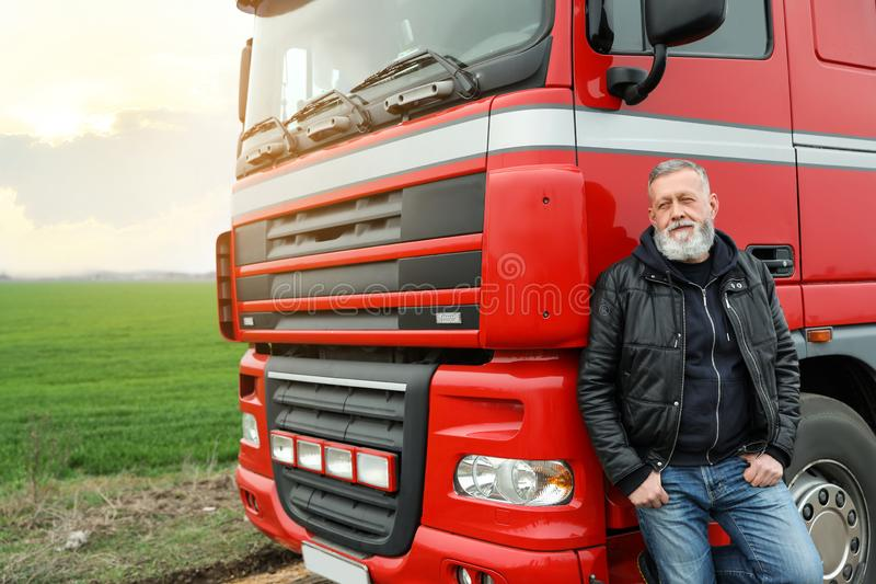 Portrait of mature driver at modern truck outdoors. Space for text royalty free stock photography