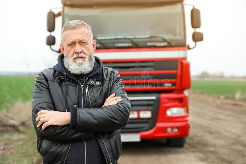 Portrait of mature driver at modern truck. Outdoors royalty free stock photos