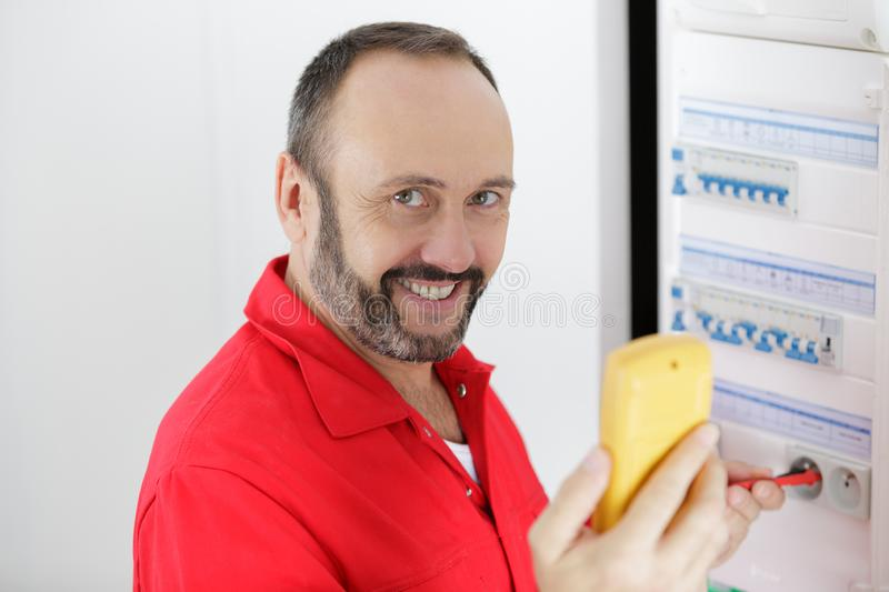Portrait mature electrician testing fusebox with multimeter stock photos