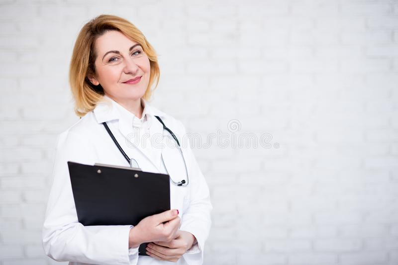 Portrait of mature female doctor or nurse holding clipboard over white wall with copy space stock photos