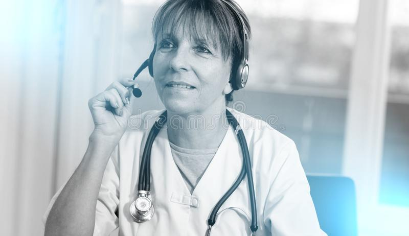 Portrait of female doctor during online medical consultation. Portrait of mature female doctor during online medical consultation royalty free stock photo